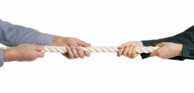 two people holding on to rope playing tug of war